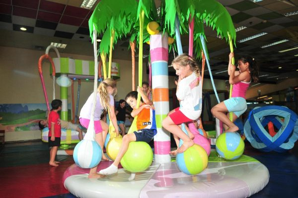 Дети катаются на аттракционе в парке развлечений