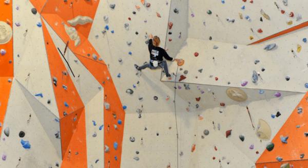 Девушка поднимается по стене на скалодроме