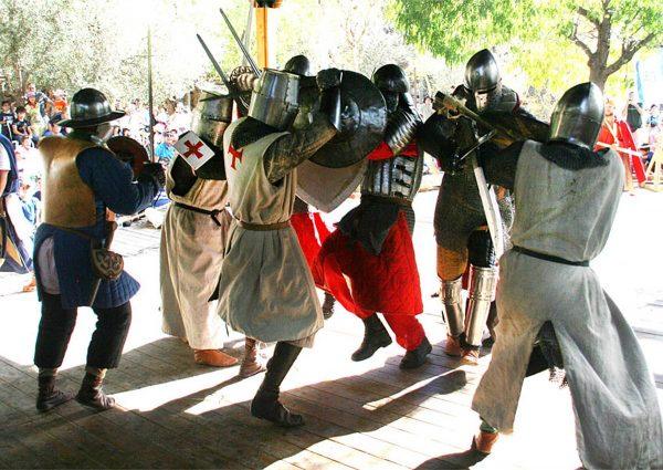 Мужчины в одеждах рыцарей сражаются на турнире