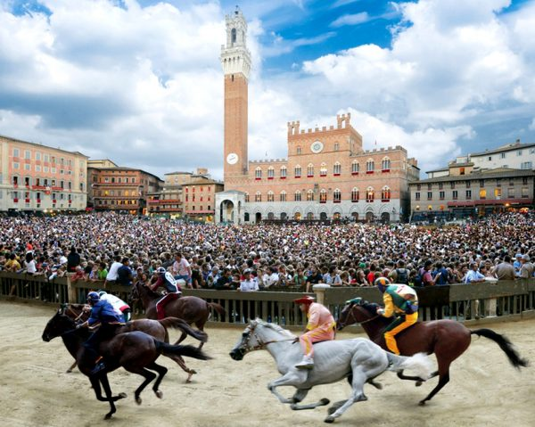 Всадники соревнуются в скачках Палио в Сиене