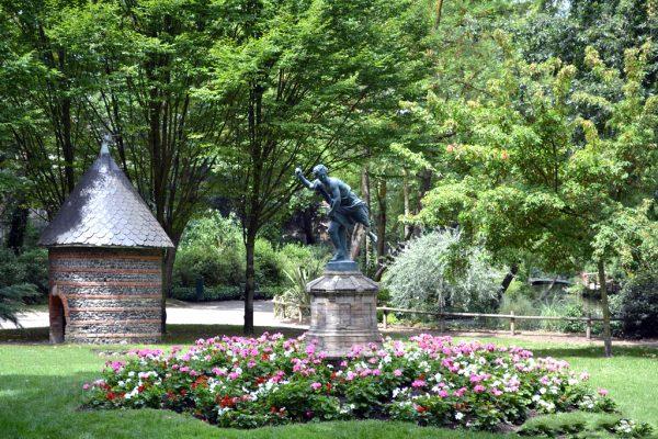 Скульптура в центре цветочной клумбы в парке