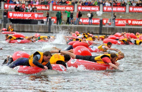 Мужчины, участники регаты, плывут на надувных плотах
