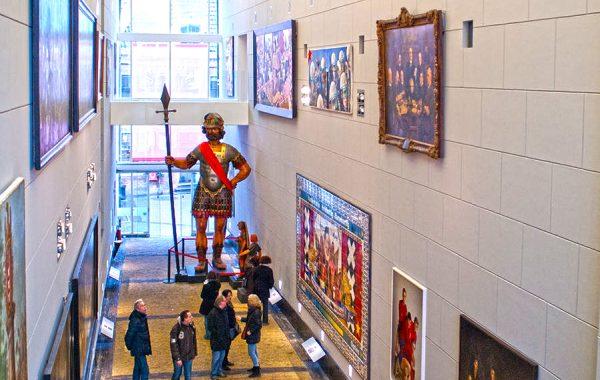 Посетители музея рассматривают картины на стенах и скульптуру