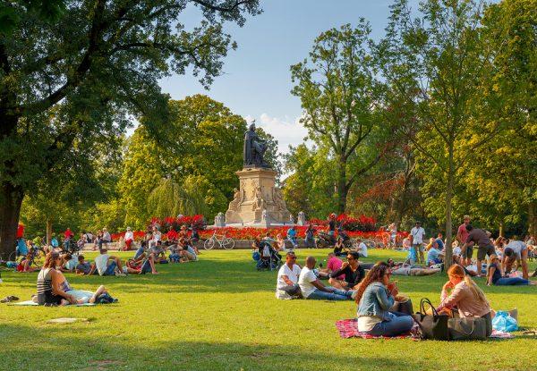 Люди отдыхают на траве в парке