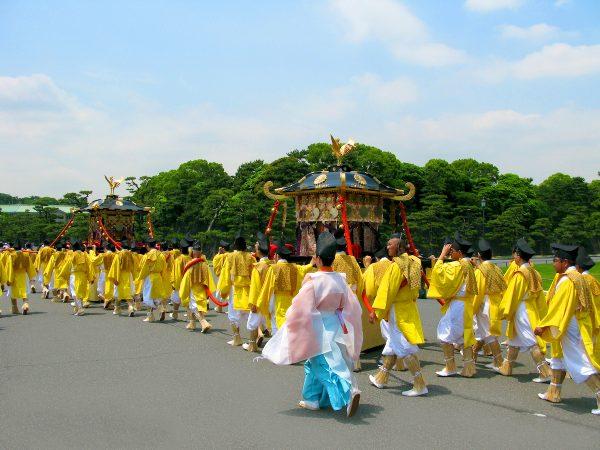 Мужчины в жёлтых одеждах, участники фестиваля Санно Мацури, идут по улице Токио