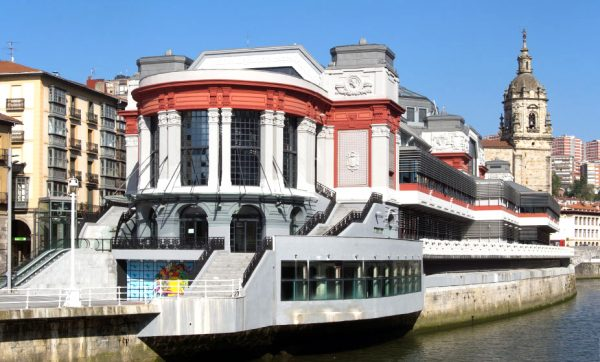 Здание крытого рынка на берегу реки в Бильбао