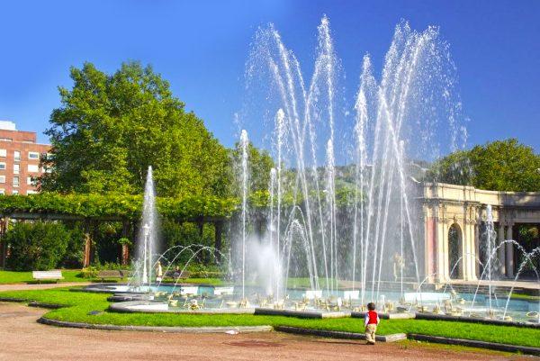 Маленький мальчик возле фонтана в парке