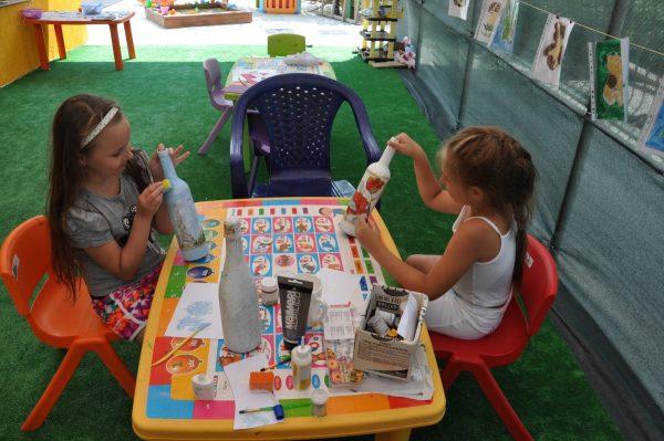 Две девочки раскрашивают бутылки