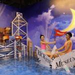 Посетители на фоне изображения Гонконга в музее оптических иллюзий