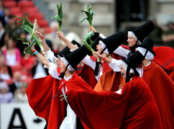 Уэльские женщины в национальных костюмах держат в руках лук-порей