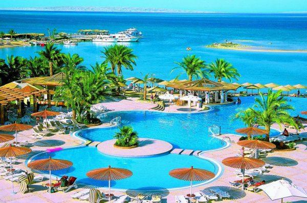 Открытые бассейны курортного отеля с лежаками и солнечными зонтами