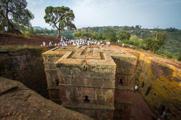 Паломники в белых одеждах возле скального храма в Лалибеле