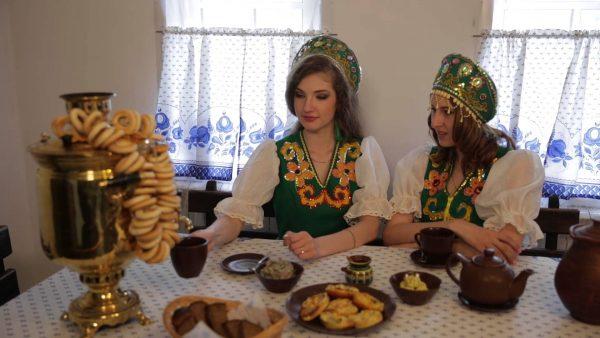 Две девушки в национальных костюмах за столом с самоваром и баранками