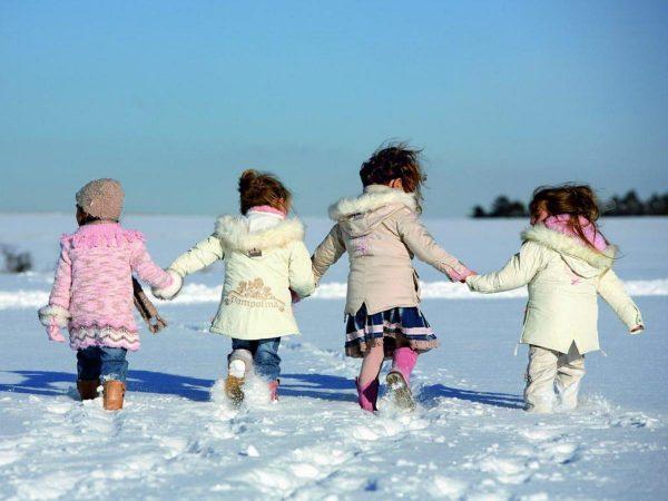 Дети, взявшись за руки, бегут по снегу