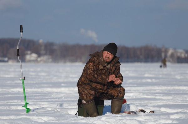 Рыбак сидит на озере зимой