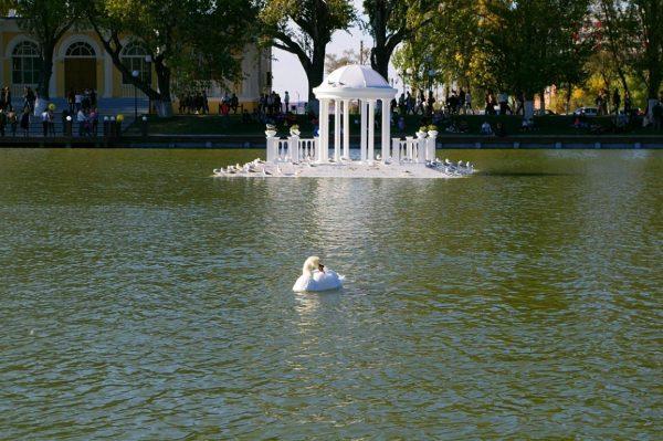 Ротонда и лебедь в озере парка Лебединое озеро в Астрахани