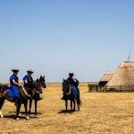 Мужчины в традиционных венгерских костюмах сидят верхом на лошадях